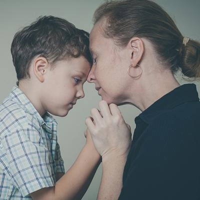 Concerned mother presses her forehead against her worried son's forehead as they clasp hands