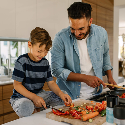 Young son chopping fresh vegetables while smiling father looks on and sautees tomatoes